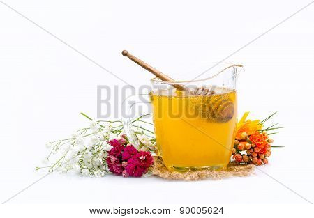 Honey jar with stick and flowers near