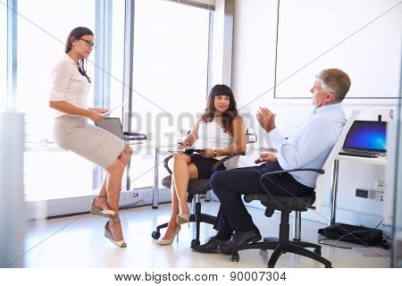 Female manager talking to colleagues in a modern office