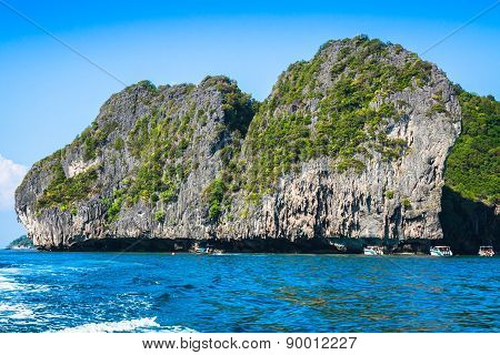 Cliff And The Clear Sea With A Boat Near Phi Phi Island In South Of Thailand