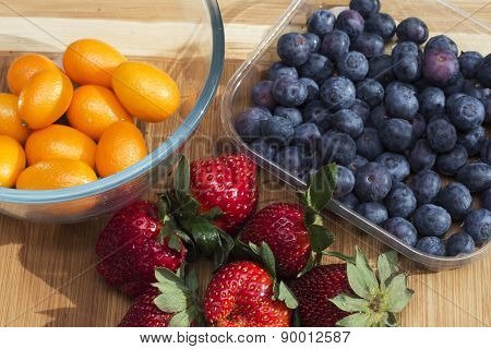 Kumquat, strawberries and blueberries on a cutting board