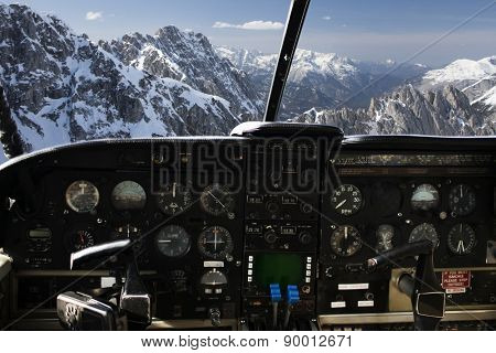 air transport, travel, technology and aviation concept - dashboard in airplane cockpit and view of snowy alps mountains behind windshield