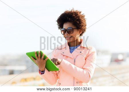 technology, lifestyle and people concept - smiling african american young woman or teenage girl with tablet pc computer outdoors
