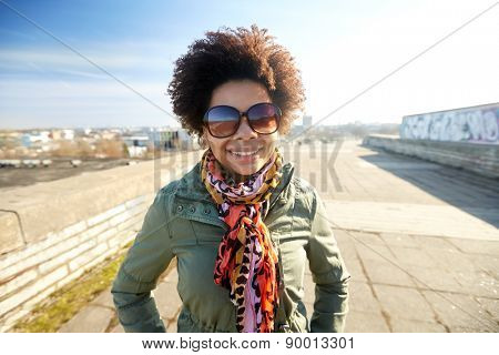 tourism, travel, people, international  and leisure concept - happy african american teenage girl or young woman in shades on city street