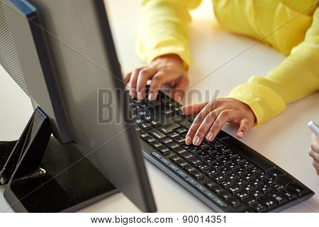 business, technology, school, people and education concept - close up of african american businesswoman or student girl hands with computer sitting at table