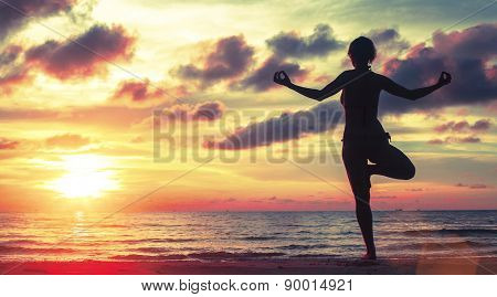 Yoga woman meditating on the beach during sunset (sunset blood colors)
