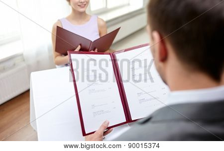 restaurant, food, eating and holiday concept - close up of couple with menu choosing dishes at restaurant