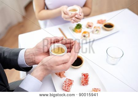 restaurant, food, people, japanese and asian kitchen concept - close up of couple drinking tea at restaurant