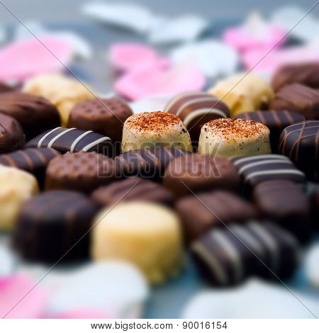 Romantic chocolate truffles and white roses heart shape setup square composition