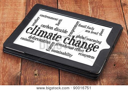 climate change word cloud on a digital tablet against rustic barn wood