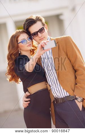 Young couple photographing themselves on a smartphone outdoors in the city.