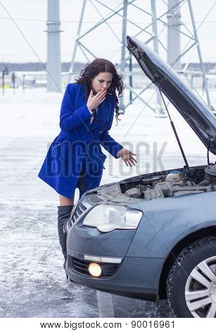 Surprised woman looking under the hood of the broken machine
