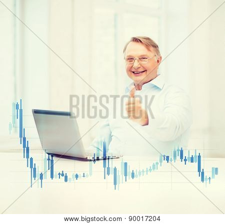 technology, money, oldness and lifestyle concept - old man in eyeglasses with laptop computer and forex chart at home showing thumbs up