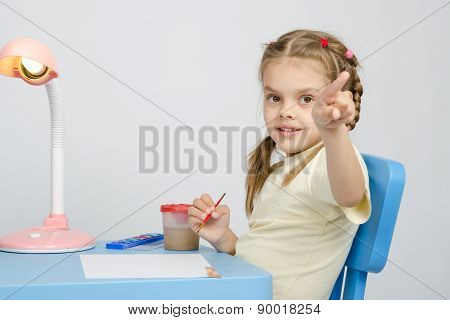 Girl Painting Paints At Table, Points The Finger