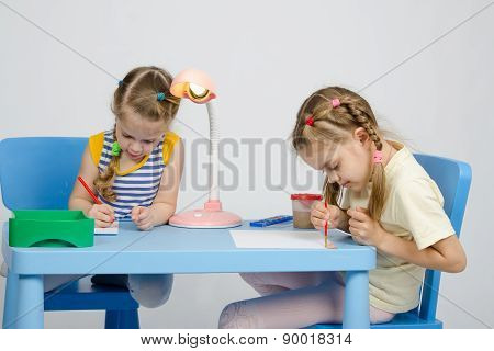 Two Girls Drawing At Table Draw Paints And Pencils