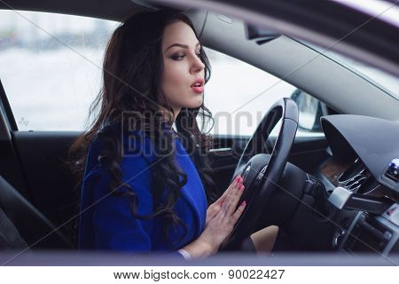 Attractive woman looks pensively into the windshield of the car and thinks as she leave the car park