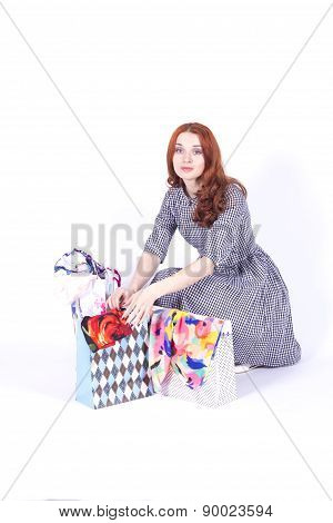 Attractive redhead woman contemplates gift bags