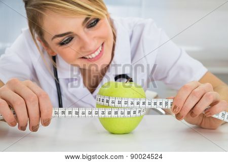Female Dietician Measuring Green Apple