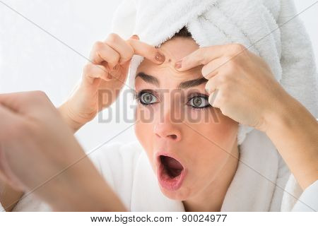 Shocked Woman Looking At Pimple On Forehead