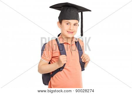 Schoolboy looking at the camera, carrying a backpack and wearing a graduation hat isolated on white background