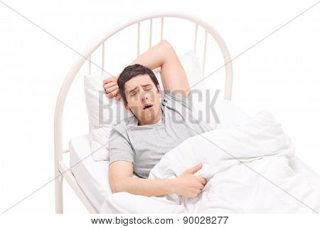 Young man sleeping in a bed and having nightmares isolated on white background