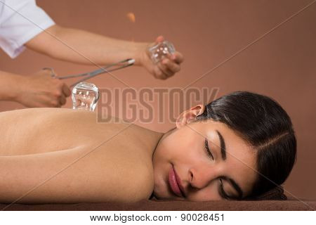 Person Holding Lit Camphor And Cup