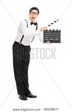 Full length portrait of a young movie director holding a clapperboard and looking at the camera isolated on white background