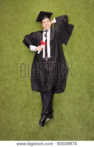 Vertical shot of a pensive young college graduate holding a diploma and lying in a grass field