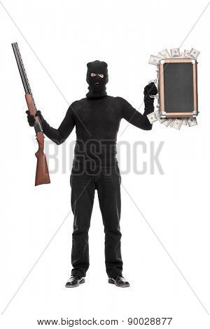 Full length portrait of a masked criminal holding a briefcase full of money in one hand and a shotgun rifle in the other isolated on white background