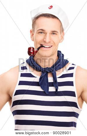Vertical shot of a young sailor smoking tobacco from a brown pipe and looking at the camera isolated on white background