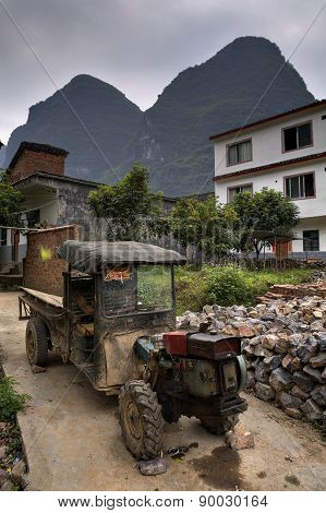 Battered Ancient Farmer Tractor Stands In Peasant Village, Guangxi, China.