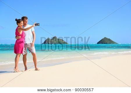 Couple on beach vacation taking selfie photograph using smartphone, Lanikai beach, Oahu, Hawaii, USA with Mokulua Islands. Couple holding smart phone camera.