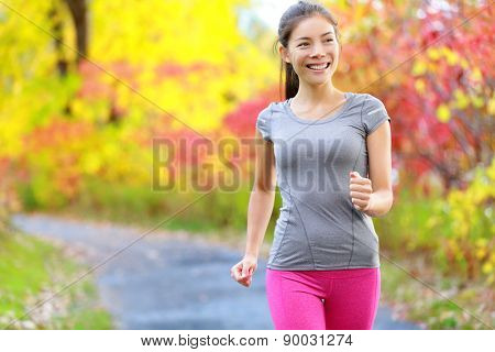 Woman power walking nordic speed walk and jogging and running lightly in forest in spring or summer. Sport fitness girl sports training and working out living healthy active lifestyle in forest.