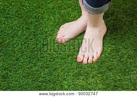 Woman legs injeans standing  on green grass
