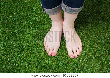 Girl legs in jeans standing  on green grass