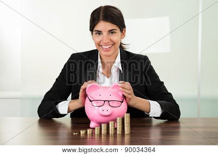 Businesswoman With Piggybank And Coins Stacks