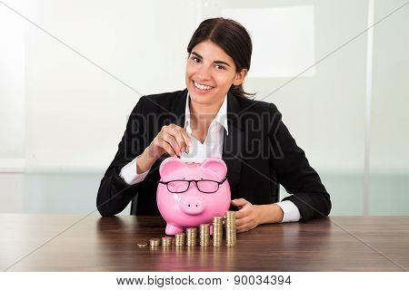 Businesswoman Inserting Coin In Piggybank