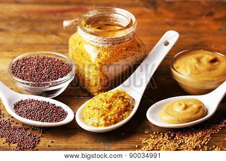 Mustard seeds, powder and sauce in spoons, bowls and glass jar on wooden background