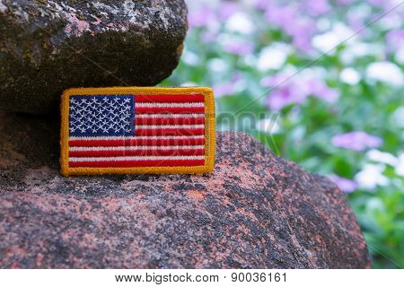 Rounded American flag patch on rock with purple flower background