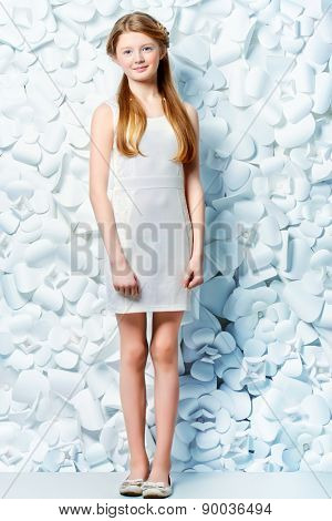 Beautiful blonde teen girl wearing white dress posing by a background of white paper flowers. Beauty, fashion. Full length portrait.
