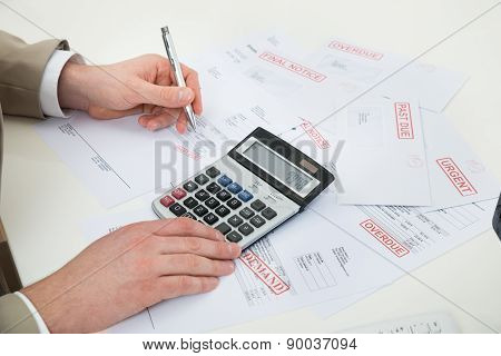 Businessperson Hand Calculating Bills