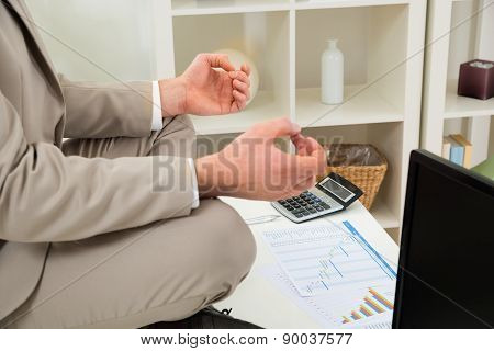 Businessman Hand Meditating At Workplace