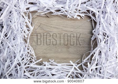 Frame of paper strips from shredder on wooden table, closeup