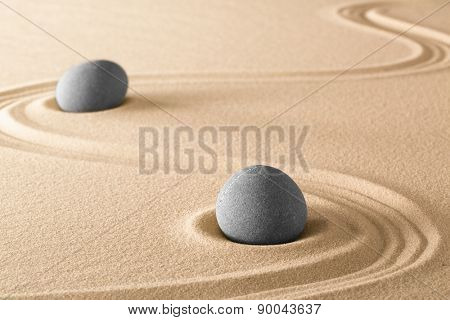 zen stones and lines in sand of Japanese garden. Spa wellnes therapy background. Purity harmony and balance.