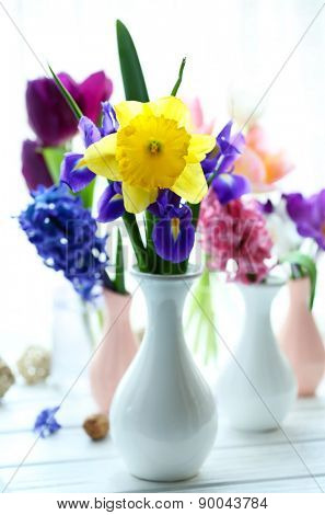 Beautiful bouquets of spring flowers on windowsill background