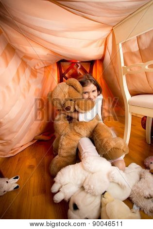 Girl In Pajamas Playing With Plush Teddy Bear At Bedroom