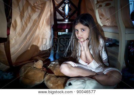 Scared Little Girl Sitting On Floor At Creepy Dark Night