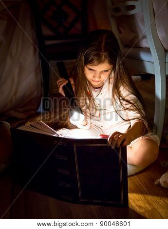 Little Girl Reading Book Under Blanket At Night