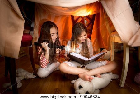 Cute Girls Sitting Under Blankets And Reading Book With Flashlight