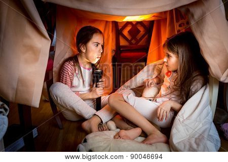 Elder Sister Telling Scary Story To Younger One At Late Night