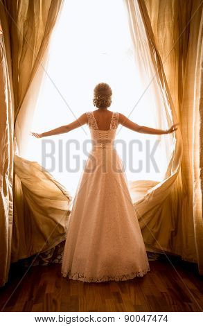 Toned Shot Of Beautiful Bride Posing At Window In Hotel Room